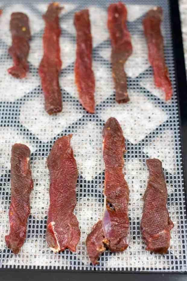 Deer jerky on dehydrator trays ready to be dried