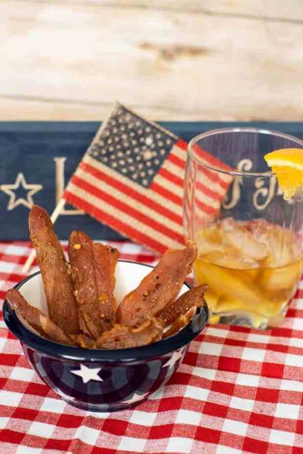 Citrus Bourbon Jerky with flag and bourbon in a glass
