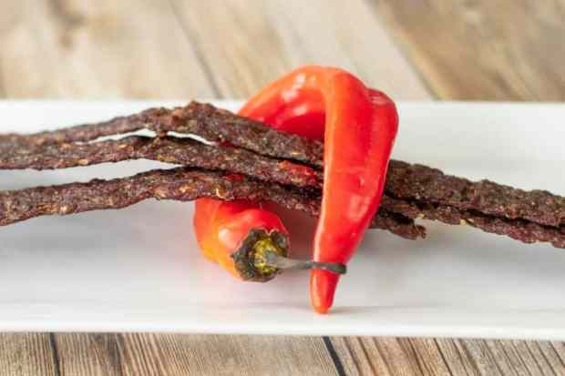 Fiery ground beef jerky wrapped in banana pepper on plate
