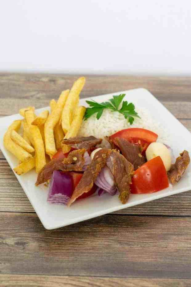 Peruvian Turkey jerky on a plate with rice and french fries