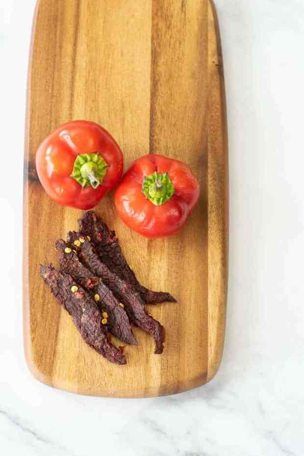 Cherry bomb beef jerky on cutting board with peppers