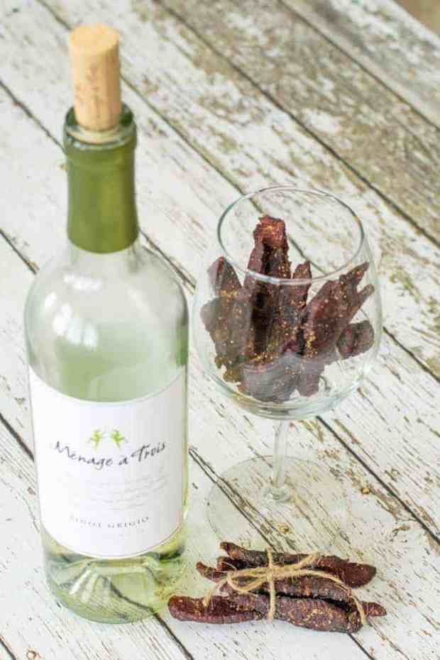 Bottle of white wine on wooden table next to a wine glass with beef jerky inside