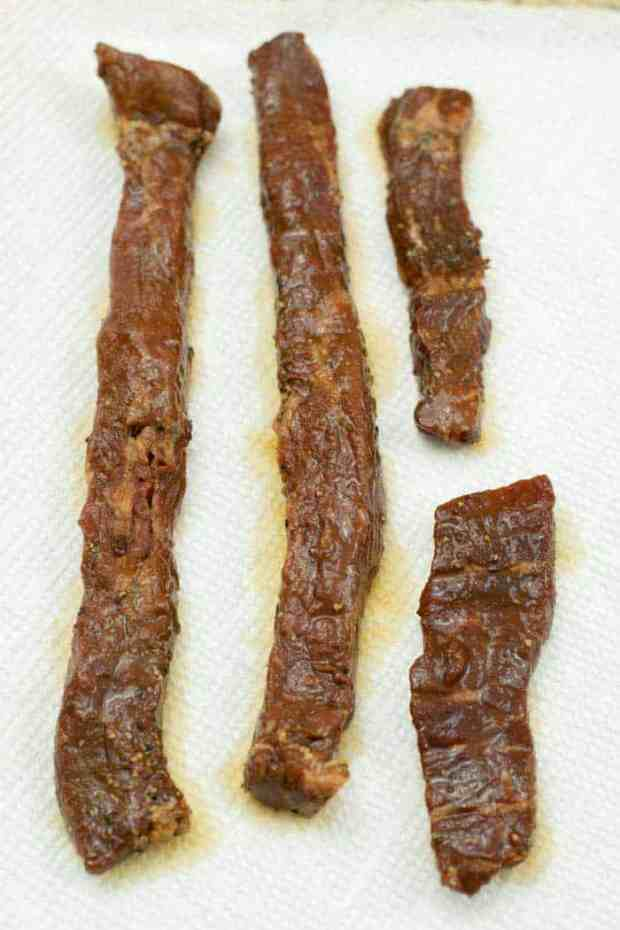 Patting jerky strips of marinade dry with paper towels