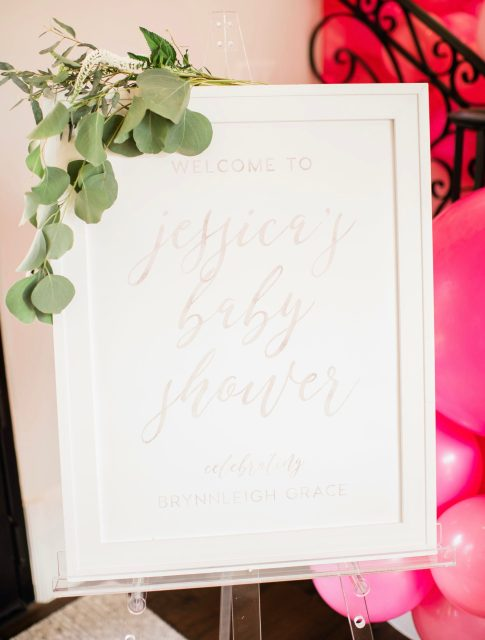 Cute Pink Baby Shower Ideas featured by top Houston lifestyle blogger and expecting mom, Jessica Crum.   Pink Baby Shower by popular Houston motherhood blogger, Jessica Crum: image of a baby shower welcome sign with some fresh green draped on it.