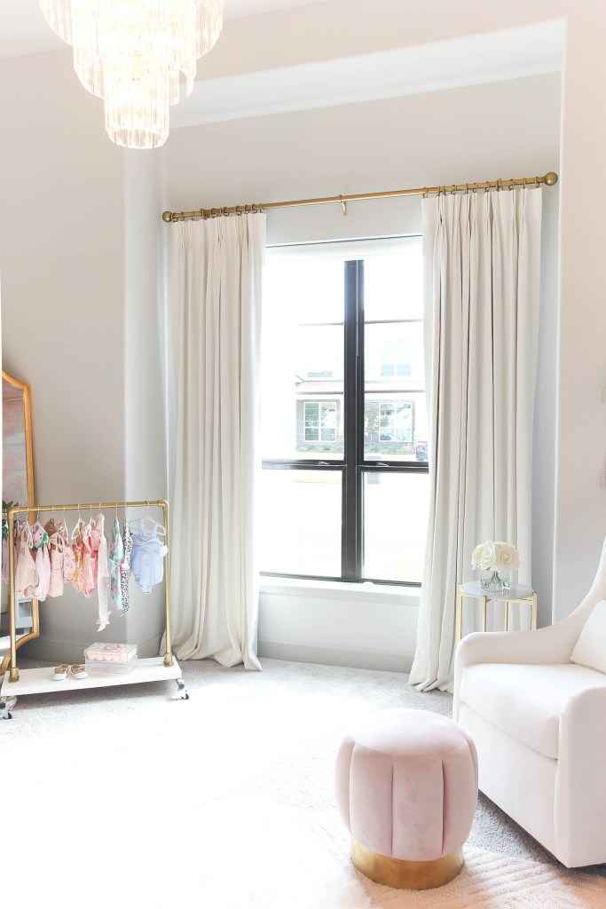 Girl Nursery by popular Houston motherhood blogger, Jessica Crum: image of a nursery decorated with a Boutique Rugs Bellaghy Mirror, Etsy Childrens standard rack, La Vie En Rose Le Medium rose box, Mud Pie clothes, Angel dear clothes, Target tuft ottoman, Pottery Barn Kids Frye rug, white glider chair, crystal chandelier, and Willow Bloom Home drapes hanging on a Pottery Barn Brass Curtain Hardware Collection.
