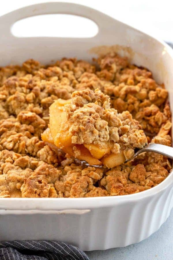 Apple crisp from the oven with golden crunchy topping in a white dish