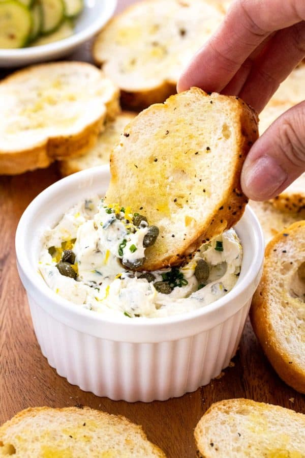 dipping a crostini into a small white bowl