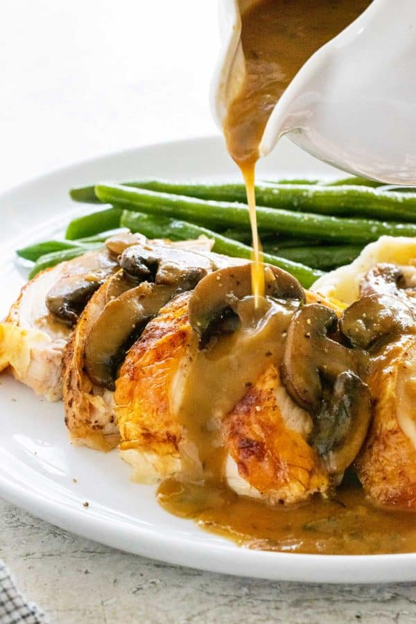 pouring gravy over a plate of chicken and green beans