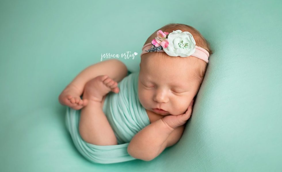 Newborns · newborn baby girl wrapped in aqua laying on aqua backdrop during newborn session with jessica ortiz