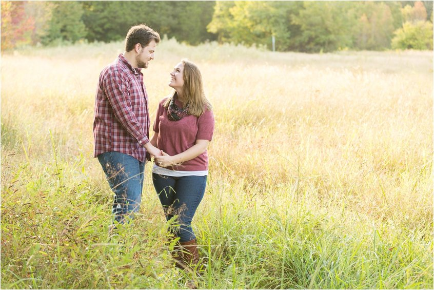 virginia beach fall engagement couple holding hands in a field