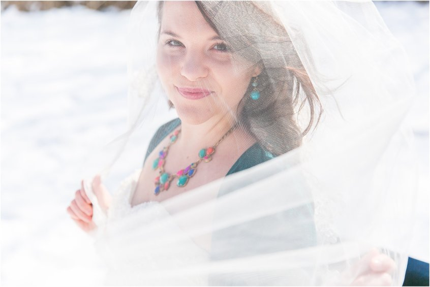 bridal portrait in the snow bride playing with veil in the wind