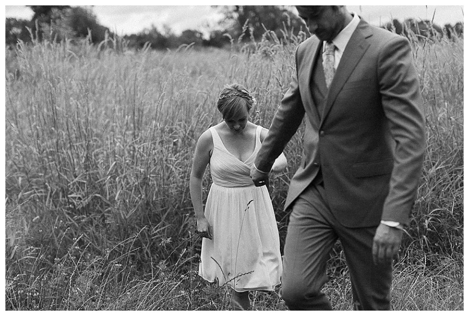 Black and white image of bride and broom in field at Red Barn Studios in Chehalis, WA