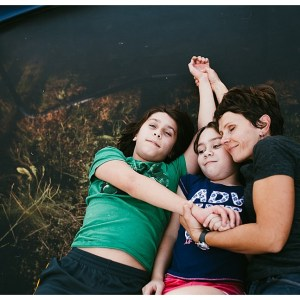 mom and two tennage children cudling together on trampoline by Seattle based photographer Jesica Uhler Photography