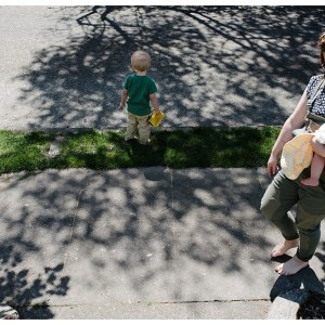 mom holding baby while son plays in front yard by Lifestyle photographer Jessica Uhler in Seattle, Tacoma