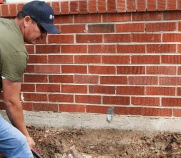Crew working on foundation with brick wall background