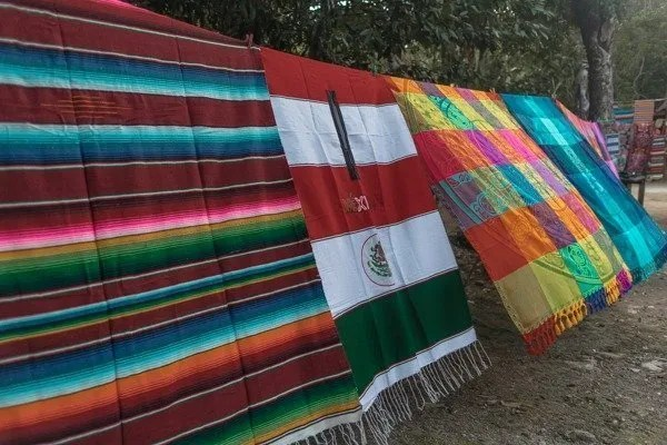 Color blankets hanging of a clothes line and swaying in the wind.