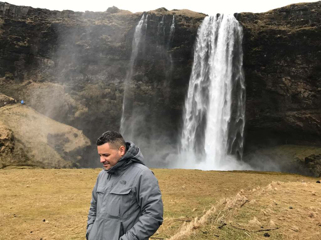 Man standing in front of a waterfall in Iceland