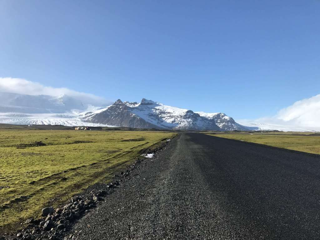 An unpaved road leading towards white capped mountains in Iceland
