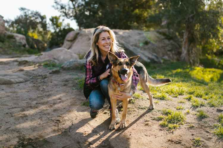woman in purple long sleeve shirt and blue denim jeans sitting beside brown dog
