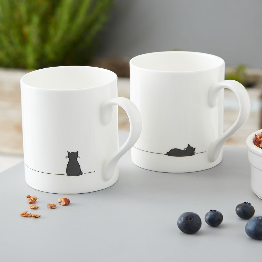 A set of bone china mugs with sitting cat and sleeping cat illustrations from Jin Designs.