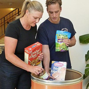 photo of woman and man adding items to food bank barrell