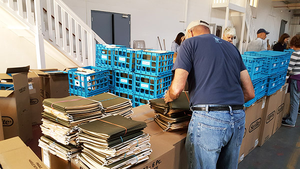 JFCS volunteers prepare file boxes for distribution. The donated cartons are designed to easily store and transport paperwork, recovery claims, and receipts after a natural disaster.
