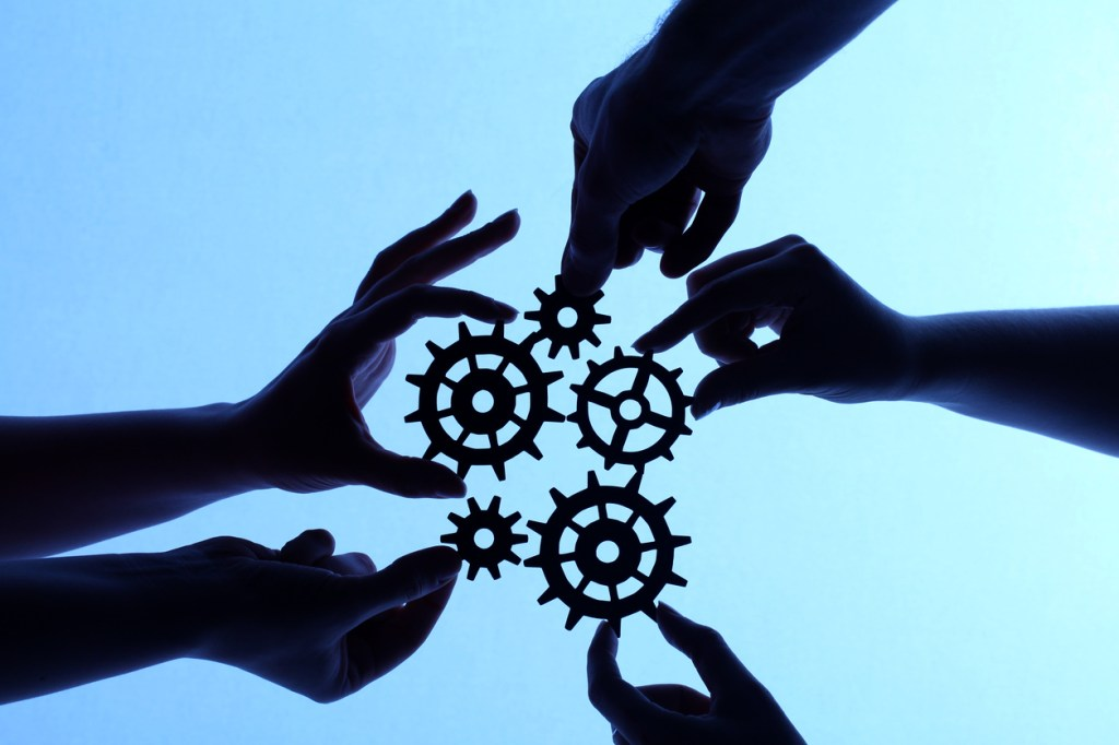 Hands and gears working together in silhouette