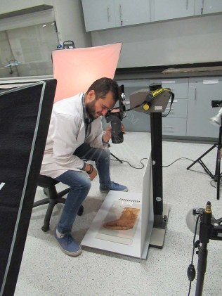 Mr Islam taking photos of the textile artifacts