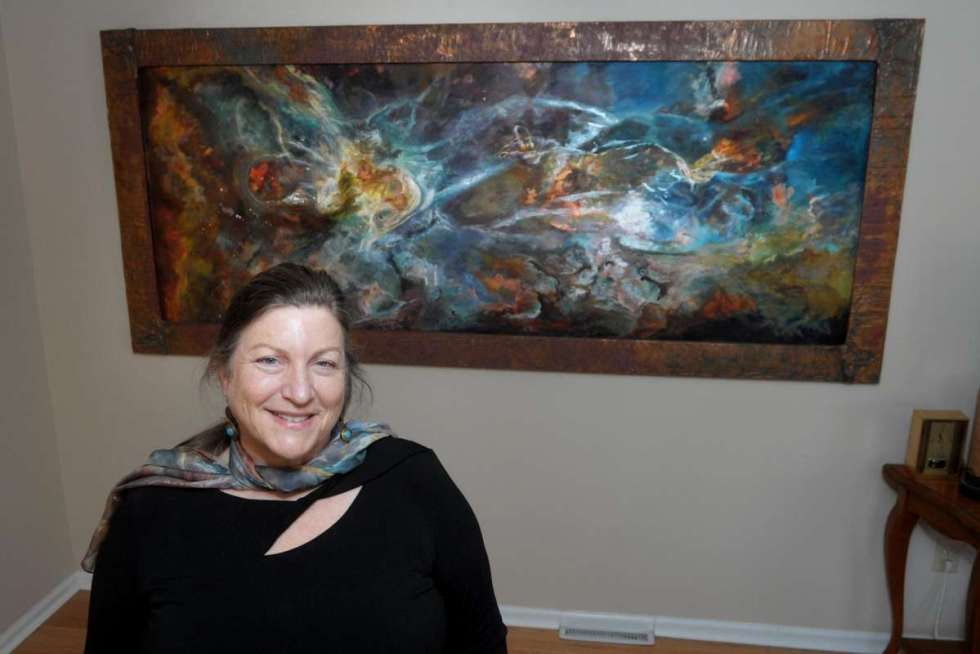 Jill Nichols poses in front of her painting 'Phi' in her home and studio in Shelton, Conn. Jan. 22, 2021. A copy of the painting currently hangs in the Vatican Observatory Museum