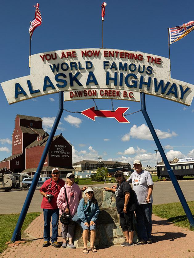 Gang under ALCAN Highway sign,