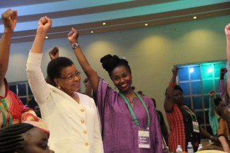 Graca Machel and other participants shout for power during a presentation by Emmanuel Jal.