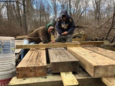 Volunteers Dan and Brendan Welsh work on the railing supports for bridge #2