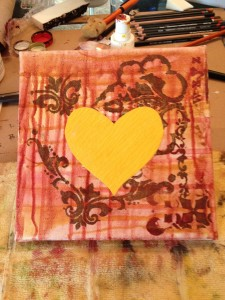 a photo of the start of a collage with a yellow heart focal point