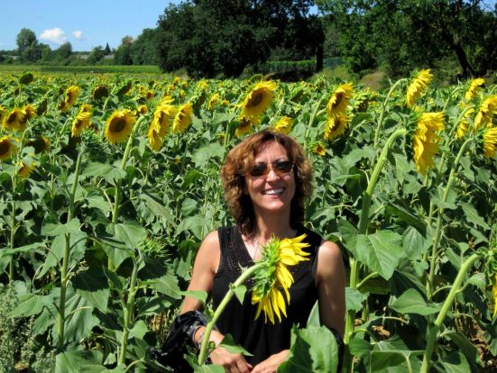Joan Jakel standing in a field of sunflowers in Tuscany Italy where she celebrated achieving her dreams and goals as she created her inspired life