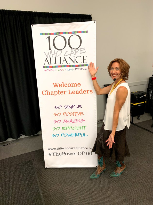 An image of Joan Jakel standing next to the 100 Who Care Alliance banner at the leadership conference. She's wearing a sleeveless cream blouse, brown skirt and kick ass brown cowboy boots with a turquoise phoenix rising on them