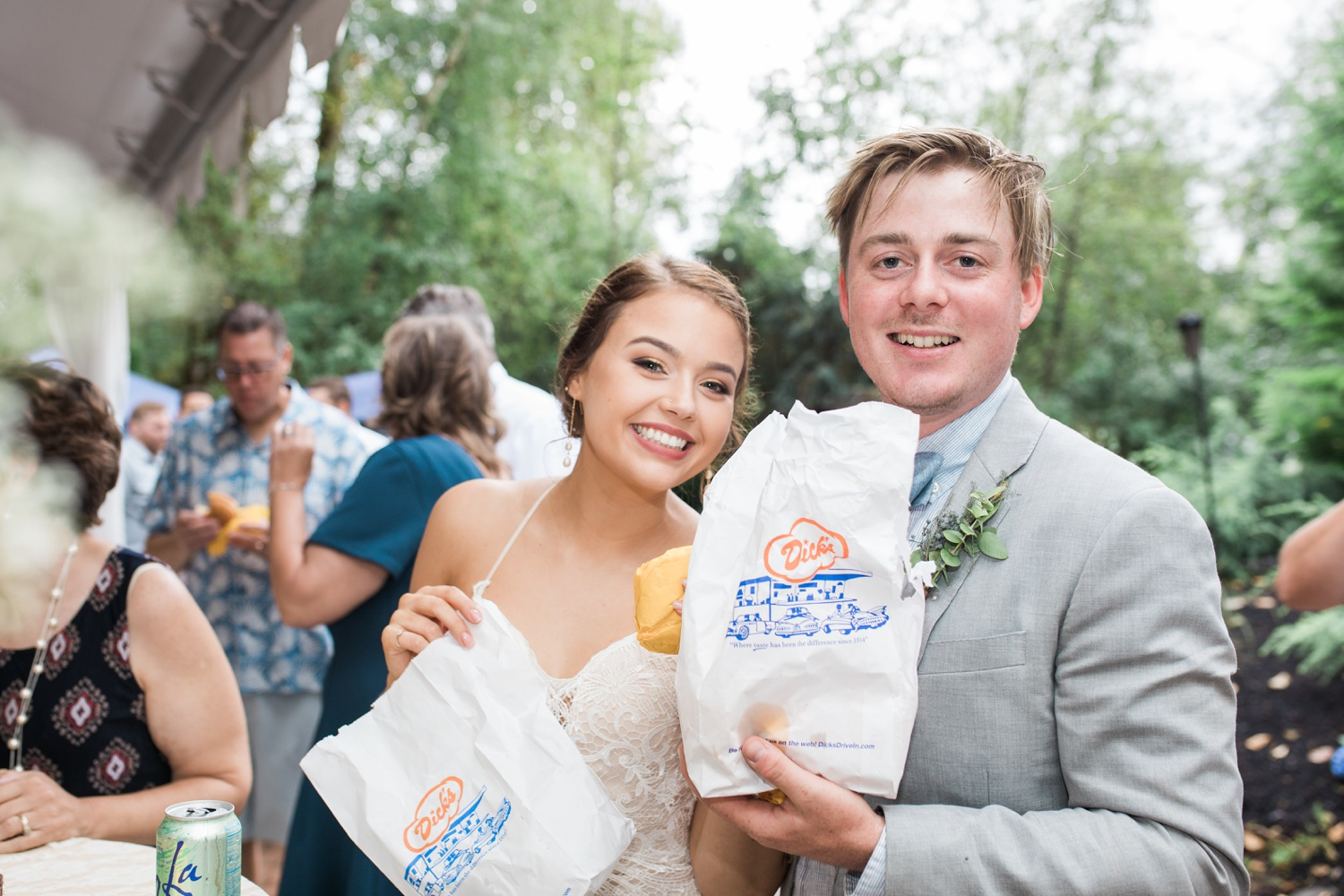 A bride and groom smile as they hold to-go bags after their summer wedding at Maroni Meadows in Snohomish, a wedding venue near Seattle, WA. | Joanna Monger Photography | Seattle & Snohomish Photographer