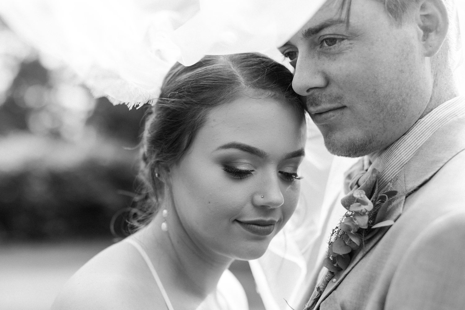 A black-and-white photo of a groom nuzzling his bride before their summer wedding at Maroni Meadows in Snohomish, a wedding venue near Seattle, WA. | Joanna Monger Photography | Seattle & Snohomish Photographer