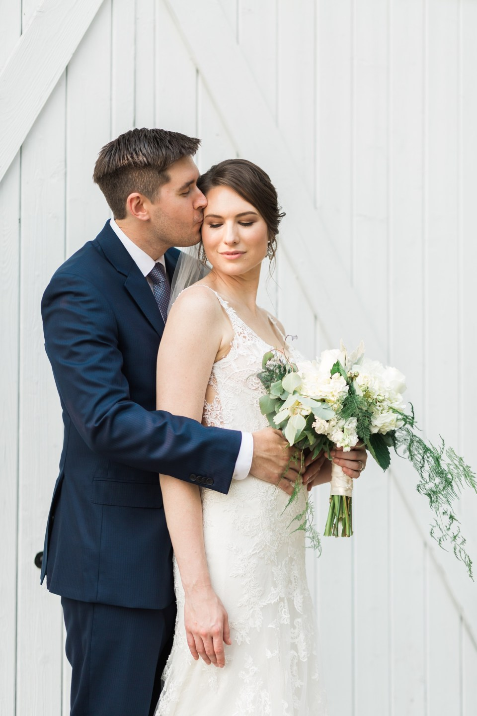 A groom kisses his bride in front of a white barn before their wedding at Chateau Lill in Woodinville, a wedding venue near Seattle, WA.   Joanna Monger Photography   Seattle & Snohomish Photographer