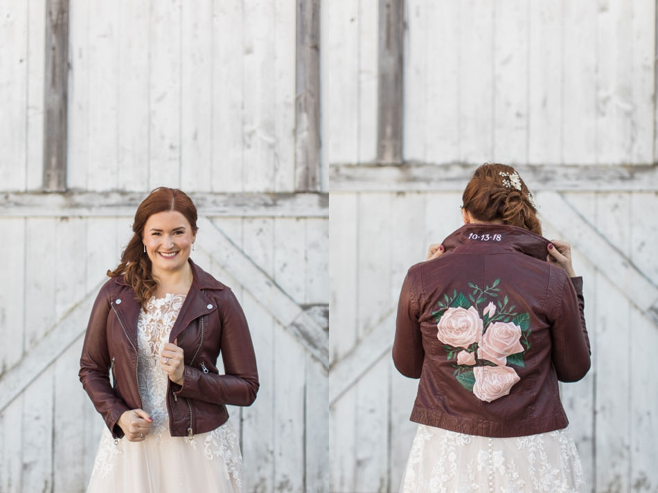 Photo of bride in front of white-wash barn in a moto jacket at Snohomish Wedding Venue Dairyland Barn near Seattle | Joanna Monger Photography