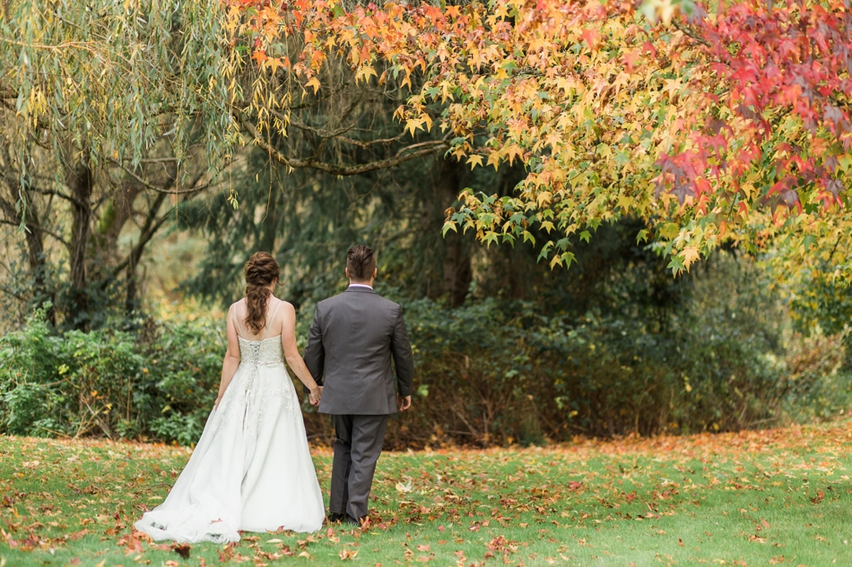 A photo of a bride and groom walking through the woods before their fall wedding at the Loft at Russell's in Bothell, a wedding venue near Seattle. | Joanna Monger Photography | Snohomish & Seattle Wedding Photographer