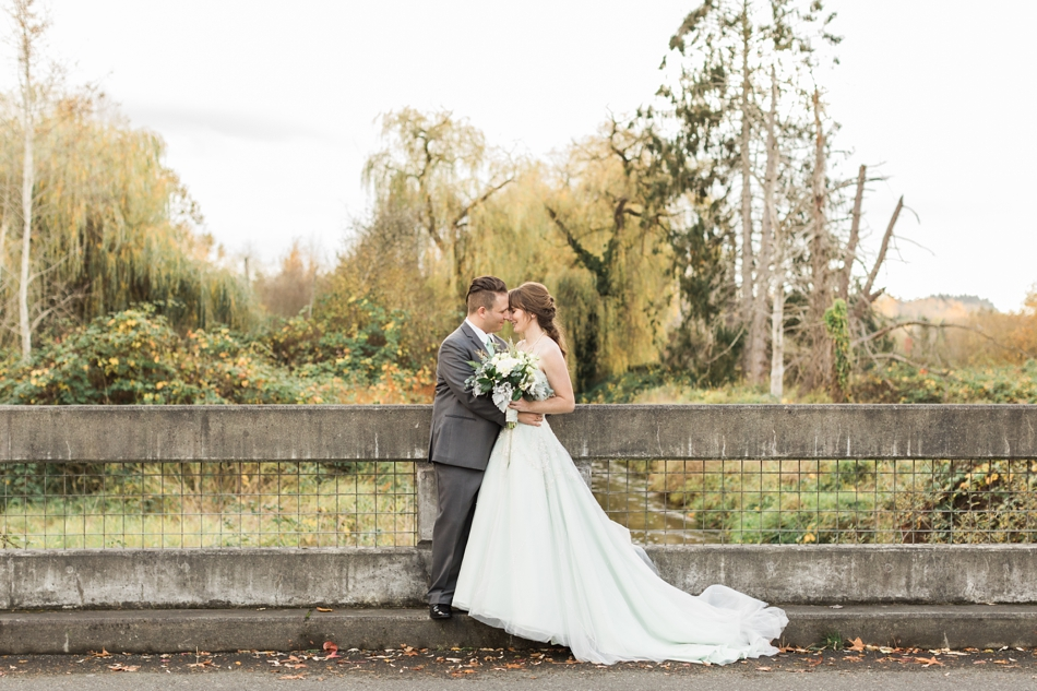 A photo of a bride and groom embracing on a concrete bridge before their fall wedding at the Loft at Russell's in Bothell, a wedding venue near Seattle. | Joanna Monger Photography | Snohomish & Seattle Wedding Photographer