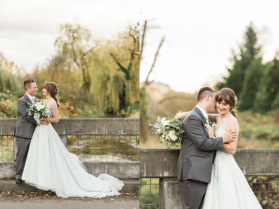 A bride and a groom look at each other and embrace while standing on a concrete bridge before their fall wedding at the Loft at Russell's in Bothell, a wedding venue near Seattle. | Joanna Monger Photography | Snohomish & Seattle Wedding Photographer