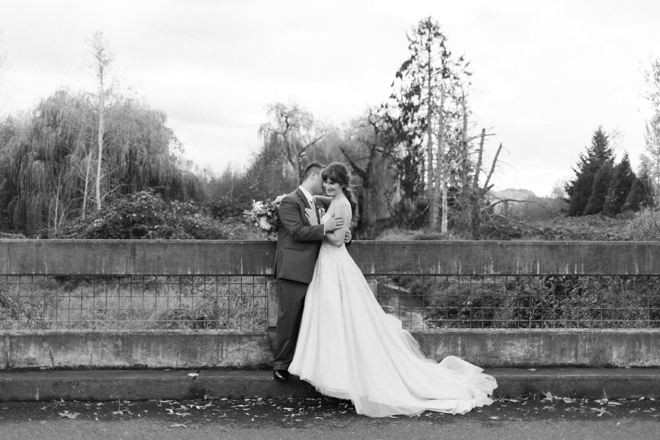 A black and white photo of a groom kisses his bride while standing on a concrete bridge before their fall wedding at the Loft at Russell's in Bothell, a wedding venue near Seattle. | Joanna Monger Photography | Snohomish & Seattle Wedding Photographer