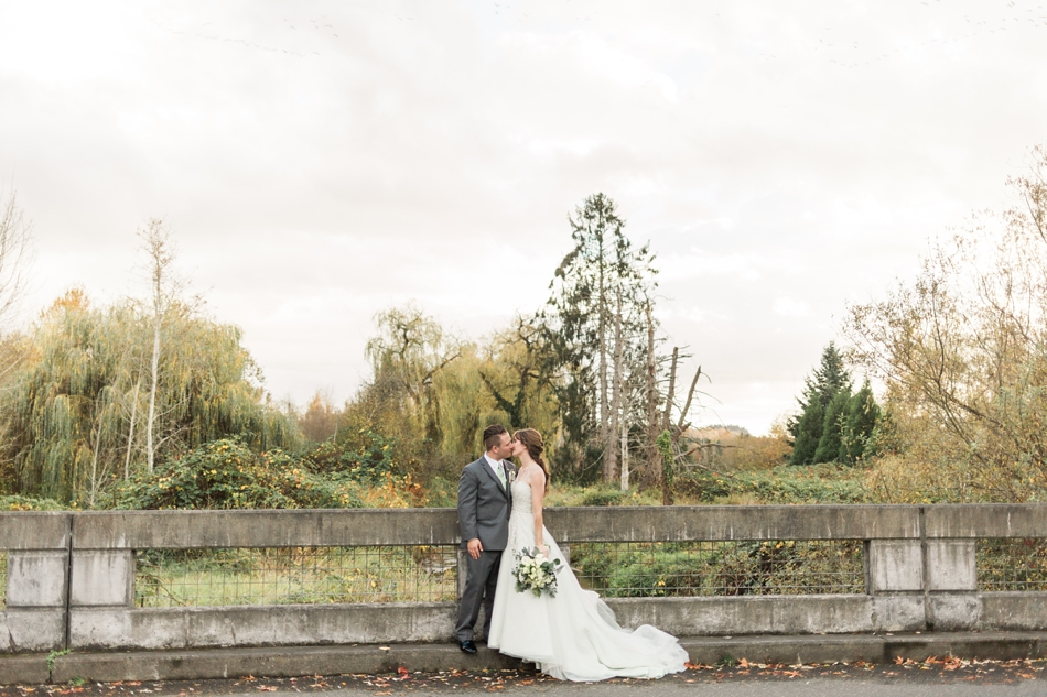 A bride and groom embrace while standing on a concrete bridge before their fall wedding at the Loft at Russell's in Bothell, a wedding venue near Seattle. | Joanna Monger Photography | Snohomish & Seattle Wedding Photographer