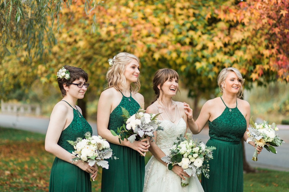 A photo of the bride and her bridesmaids, dressed in emerald green, smiling before her fall wedding at the Loft at Russell's in Bothell, a wedding venue near Seattle. | Joanna Monger Photography | Snohomish & Seattle Wedding Photographer