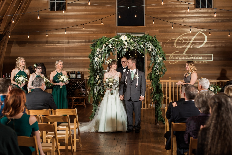 A photo of a bride and groom walking hand-in-hand down the aisle at their fall wedding at the Loft at Russell's in Bothell, a wedding venue near Seattle. | Joanna Monger Photography | Snohomish & Seattle Wedding Photographer