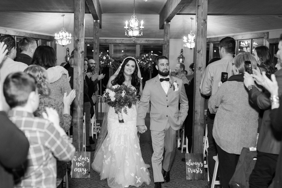 A black and white photo of a bride and groom walking down the aisle at their winter wedding at Hidden Meadows in Snohomish, a wedding venue near Seattle, WA. | Joanna Monger Photography | Snohomish & Seattle Wedding Photographer