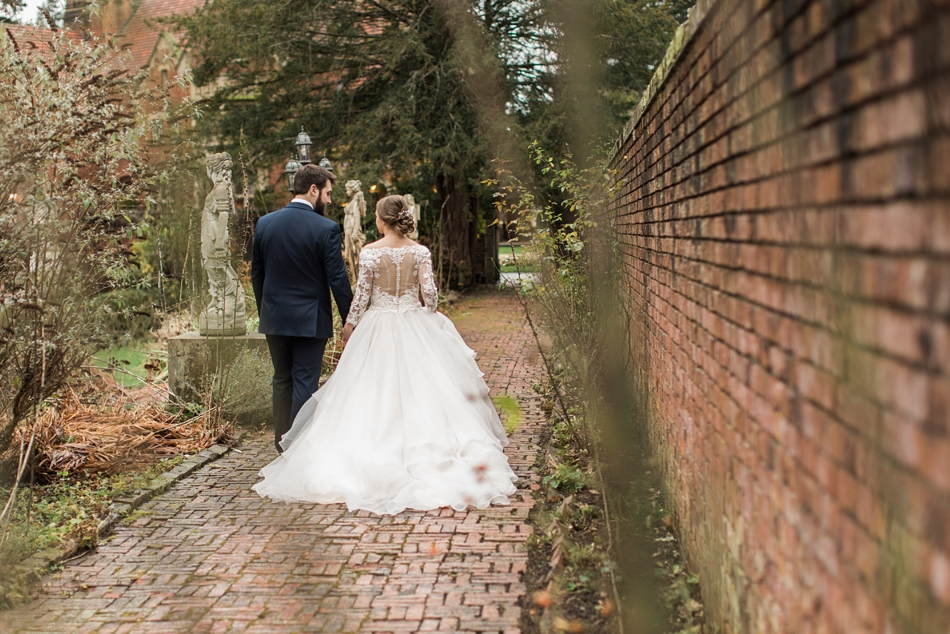 A bride and groom walk hand-in-hand on a brick path after their regal winter wedding at Thornewood Castle in Lakewood, a wedding venue near Seattle, WA. | Joanna Monger Photography | Seattle & Snohomish Wedding Photographer