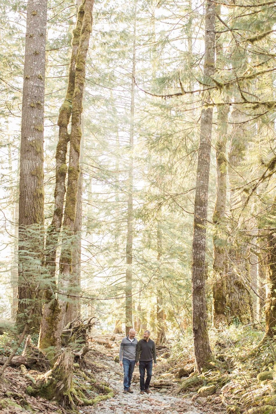 An engaged couple holds hands in the forest during their spring outdoor mountain engagement shoot in Snohomish, near Seattle, WA. | Joanna Monger Photography | Snohomish Wedding Photographer