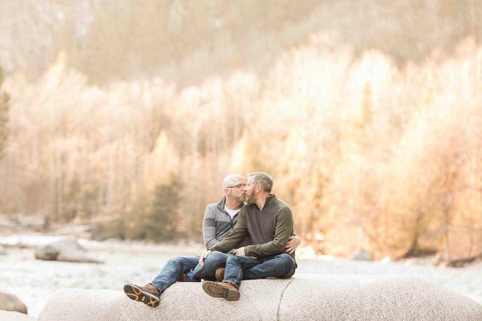 Photo of an engaged couple sitting by a river during their spring outdoor mountain engagement shoot in Snohomish, near Seattle, WA. | Joanna Monger Photography | Snohomish Wedding Photographer